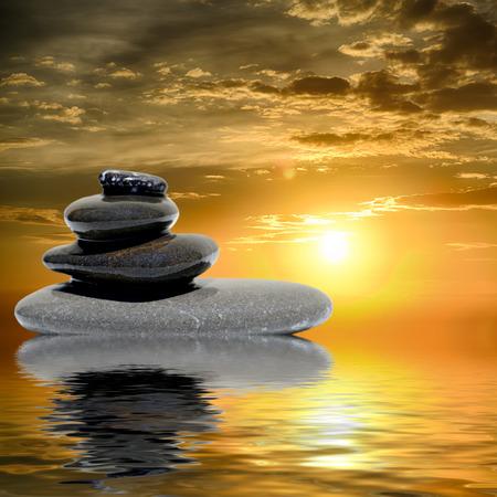 zen water: Zen massage stones at sunset reflected in water