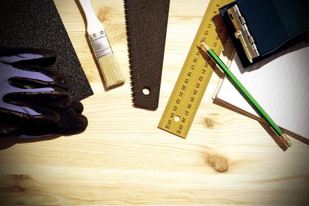 menuisier: En milieu de travail et les outils d'un menuisier ou builder.Hand vu, règle, brosse, cahier, crayon, papier de verre, et travaillent gloves.Special photo tonique dans le style vintage