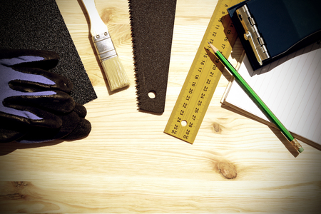 carpenter: Workplace and tools of a carpenter or builder.Hand saw, ruler, brush, notebook, pencil, sandpaper, and work gloves.Special toned photo in vintage style