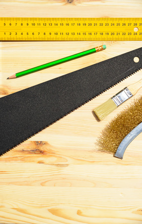 grinding teeth: Workplace and tools of a carpenter or builder-hand saw, ruler, brush, notebook, and pencil