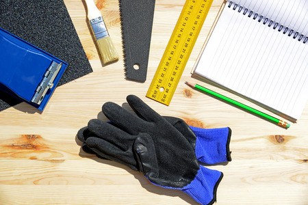 grinding teeth: Workplace and tools of a carpenter or builder.Hand saw, ruler, brush, notebook, pencil, sandpaper, and work gloves