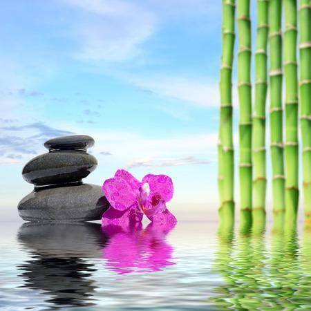 black stones: Zen spa concept background-Zen massage stones and bamboo reflected in water Stock Photo