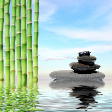 spirituality therapy: Zen spa concept background-Zen massage stones and bamboo reflected in water Stock Photo