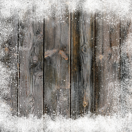 winter weather: Christmas background with old snow covered wooden planks and snow flakes and snowdrifts