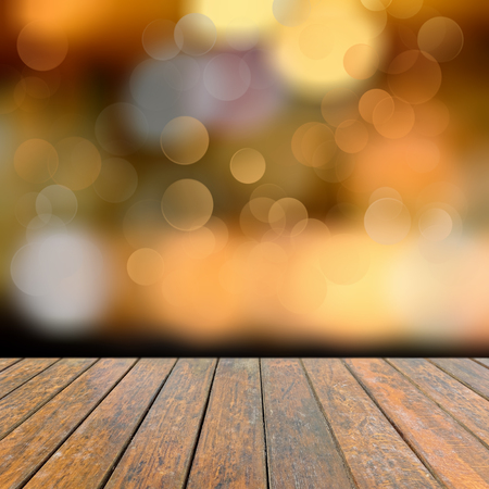 construction material: Old wooden deck table with a sparkling bokeh of party lights in the black background