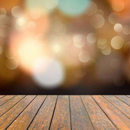 Old wooden deck table with a sparkling bokeh of party lights in the black background