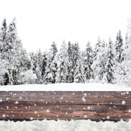 snow covered forest: Blurred winter background with snow covered forest and shabby table