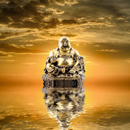 Feng Shui background. Laughing Buddha or Budai is reflected in water at sunrise
