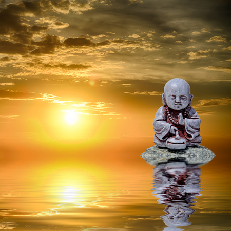 reflected: Feng Shui background. Buddha reflected in water at sunrise