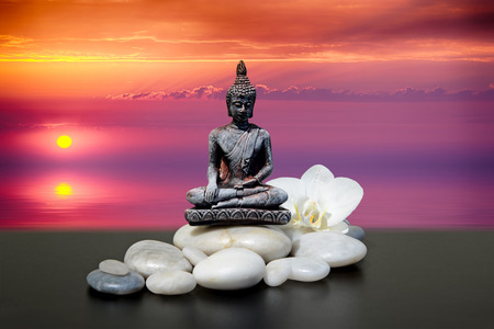fengshui: Zen or Feng-Shui background-Buddha,zen stone,white orchid flowers.In the background sunrise over the sea Stock Photo