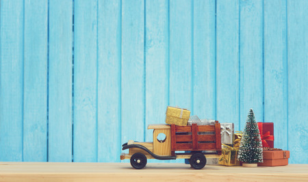 Christmas background.Toy truck carries gifts and a Christmas tree. Photo in vintage style