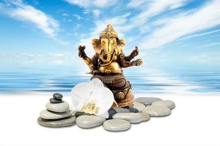 Ganesha or Ganapati,zen stone,white orchid flowers and sky reflected in water Stock Photo