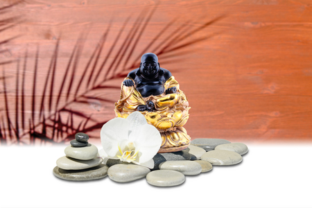 Laughing Buddha,zen stone,white orchid flowers.In the background is blurred wooden wall with palm shadow silhouette Stock Photo