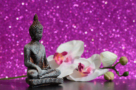 flower head: Buddha statue and a orchid flower on a bright pink shiny glitter background with bokeh Stock Photo