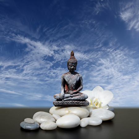 Buddha,zen stone,white orchid flowers and sky background Stock Photo