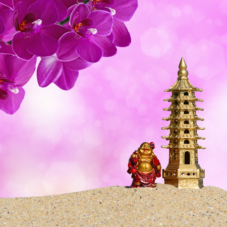 Laughing Buddha,orchid flowers and seven-storied pagoda in the sand. Symbol of good luck and prosperity in Feng-Shui Stock Photo