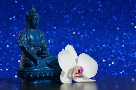 blue orchid: Buddha statue and a orchid flower on a bright blue shiny glitter background with bokeh