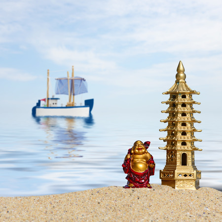 Laughing Buddha and seven-storied pagoda in the sand. Symbol of good luck and prosperity in Feng-Shui
