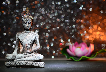 Zen Buddha statue and a lotus flower on a bright shiny glitter background with bokeh Stockfoto