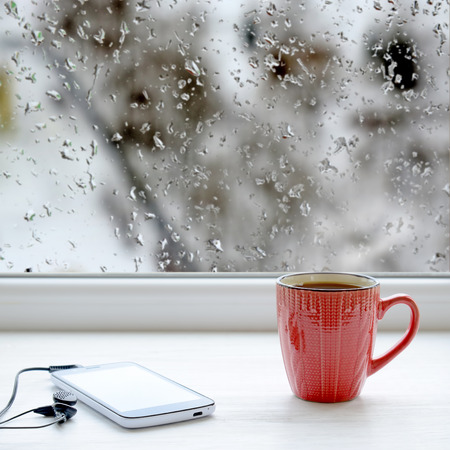 Cup of coffee, smartphone and headphones on a windowsill. In the background window with raindrops and the view of the street