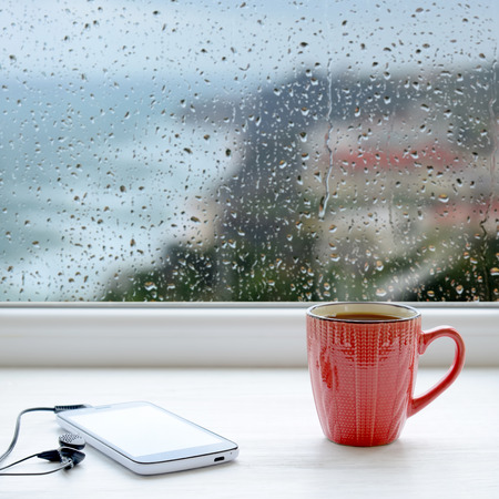 Cup of coffee, smartphone and headphones on a windowsill. In the background window with raindrops and clouds