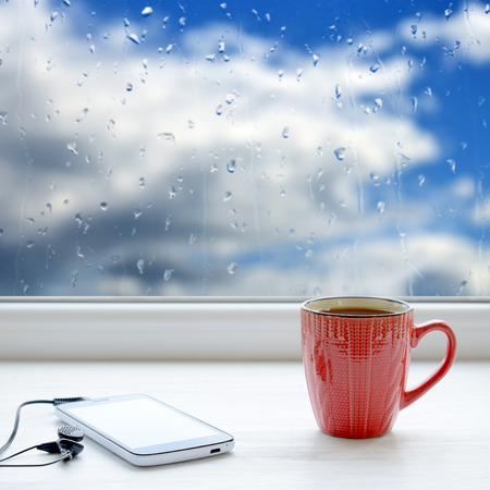 waiting posture: Cup of coffee, smartphone and headphones on a windowsill. In the background window with raindrops and clouds
