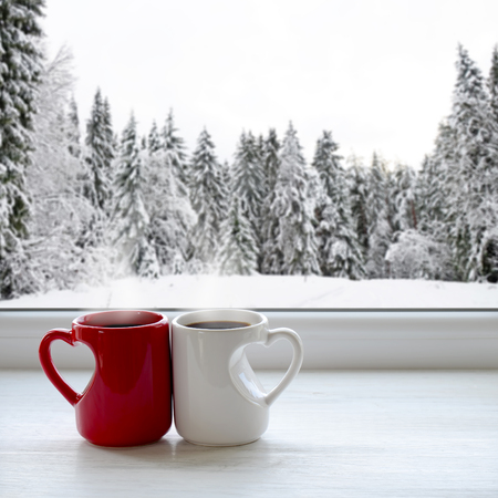 Two cups of coffee on a windowsill. In the background, a beautiful winter forest in snow