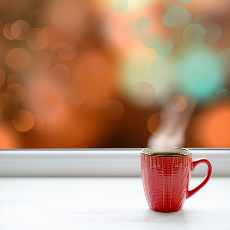 Cup of coffee on the window sill. In the background the bright lights of the city as a Christmas background