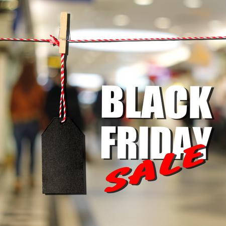 総: Black friday. Black sale tag on the background of shopping mall interior, shallow depth of focus