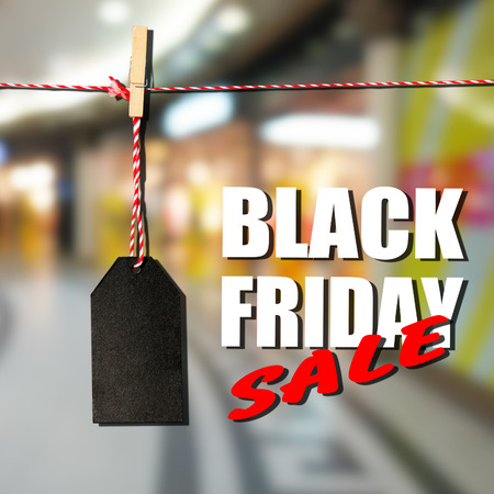 Black friday. Black sale tag on the background of shopping mall interior, shallow depth of focus