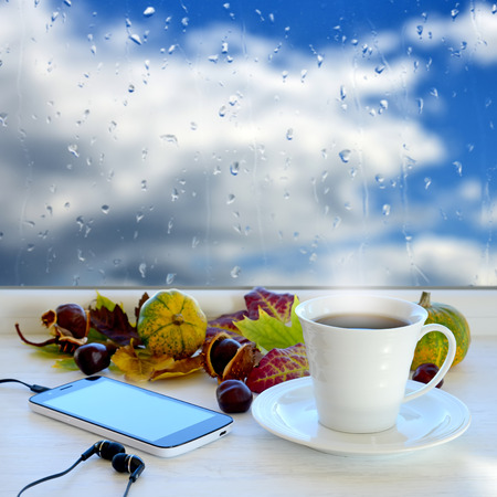 Cup of coffee, smartphone and headphones, autumn leaves, pumpkins and chestnuts on a windowsill. In the background window with raindrops and clouds