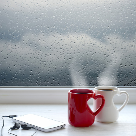 waiting posture: Two cups of coffee, smartphone and headphones on a windowsill. In the background window with raindrops and clouds Stock Photo