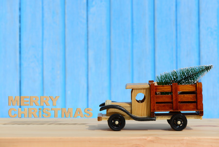 Christmas background.Toy truck carries gifts and a Christmas tree