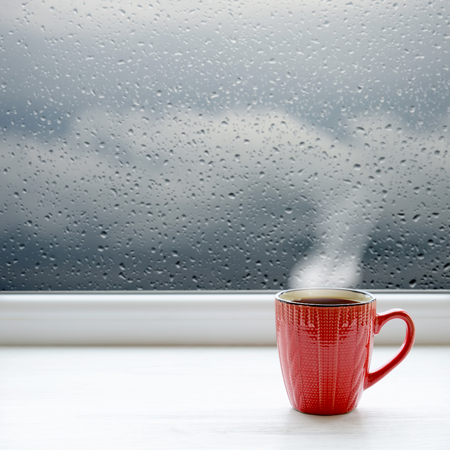 waiting posture: Cup of coffee on a windowsill. In the background window with raindrops and clouds Stock Photo