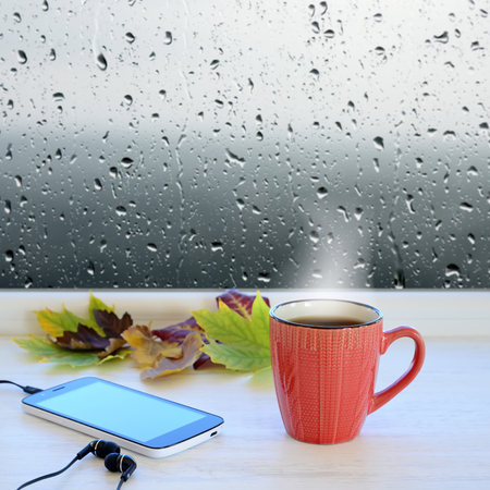 Cup of coffee, smartphone, headphones and autumn leaves on a windowsill. In the background window with raindrops and clouds Stock Photo