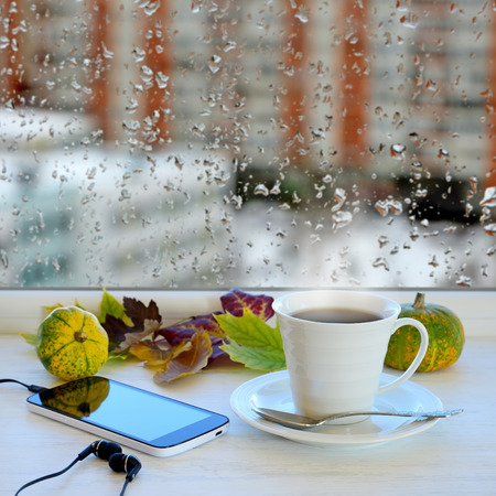 Cup of coffee, smartphone and headphones, autumn leaves and pumpkins on a windowsill. In the background window with raindrops and clouds