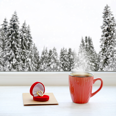 Wedding ring, note and cup of coffee on a background beautiful winter forest in snow Stock Photo