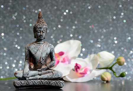 flower head: Buddha statue and a orchid flower on a bright shiny glitter background with bokeh
