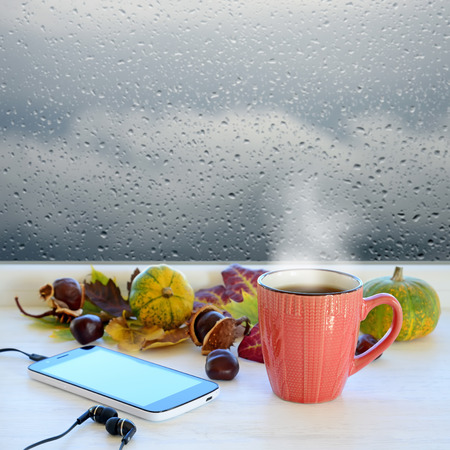 waiting posture: Cup of coffee, smartphone and headphones, autumn leaves, pumpkins and chestnuts on a windowsill. In the background window with raindrops and clouds