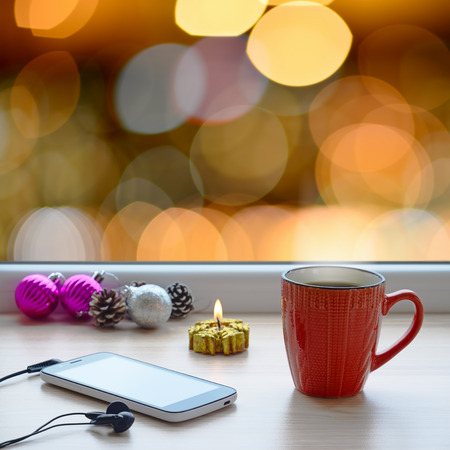 Cup of coffee, smartphone, headphones and Christmas tree ornaments on a windowsill. In the background, the bright lights of the city