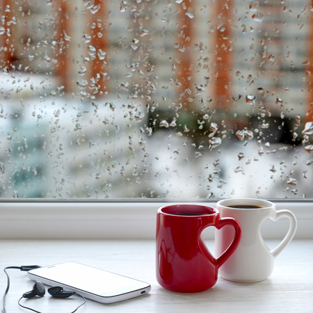 Two cups of tea, smartphone and headphones on a windowsill. In the background window with raindrops and the view of the street