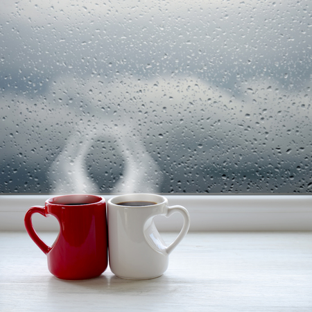 waiting posture: Two cups of tea, smartphone and headphones on a windowsill. In the background window with raindrops and clouds Stock Photo