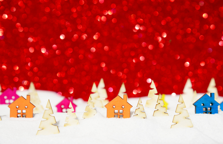 Christmas background.Fairy Village in the winter forest and pile of snow on red glitter bokeh background Stock Photo