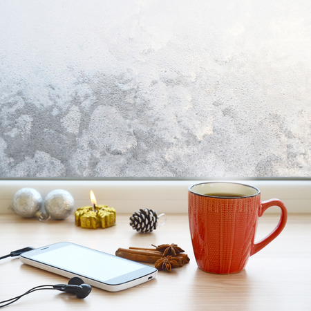 Cup of coffee, smartphone, headphones and Christmas tree ornaments on a window sill. In the background frosty pattern on window as a Christmas background