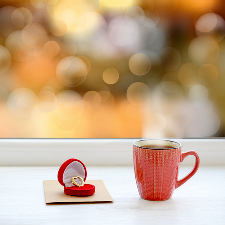 Wedding ring, note and cup of coffee. In the background the bright lights of the city as a Christmas background