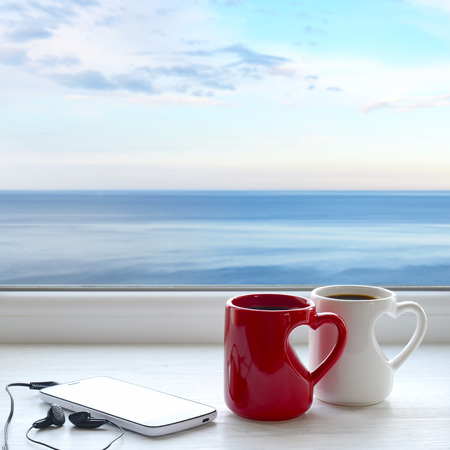Two cups of hot tea, smartphone and headphones on a window sill. In the background sea and sky Stock Photo