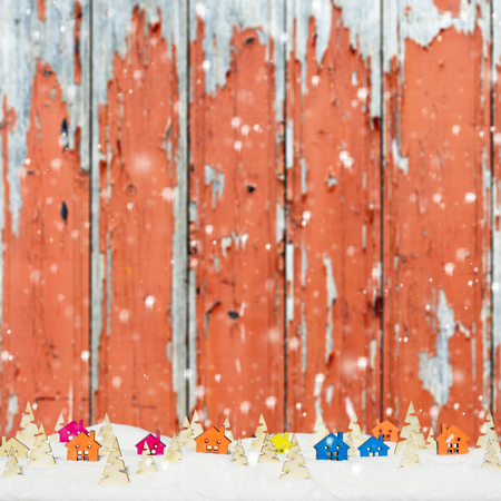 Christmas background with small wooden houses, Christmas trees and snow