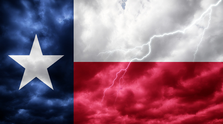 Texas flag against dark sky, clouds and lightning