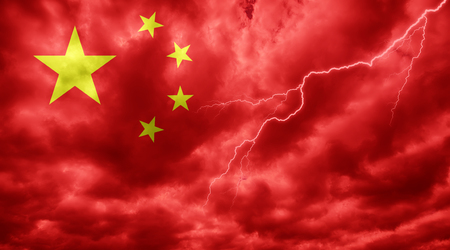 Chinese flag against dark sky, clouds and lightning