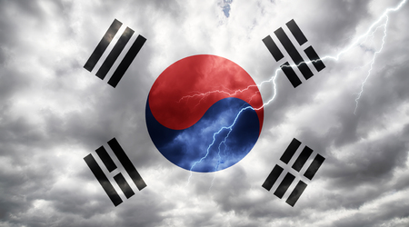 South Korean flag against dark sky, clouds and lightning